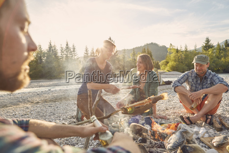 adults sitting around campfire cooking fish