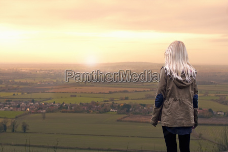 young woman watching sunrise over rural