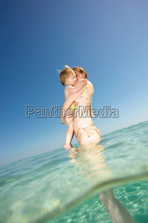 woman standing in water holding toddler