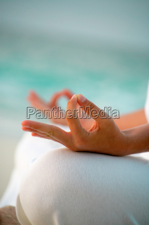 close up of womans hands meditating