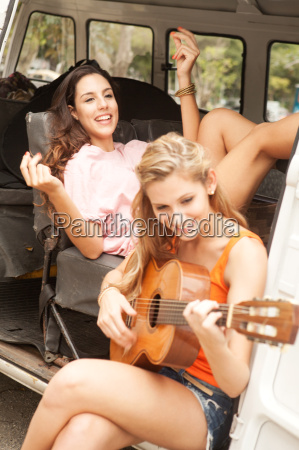 young women with guitar on camper