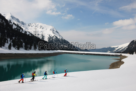 skiers by lake and mountain kuhtai