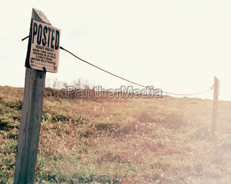fence post in field with sign
