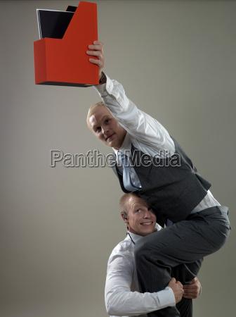 business men placing paper holder