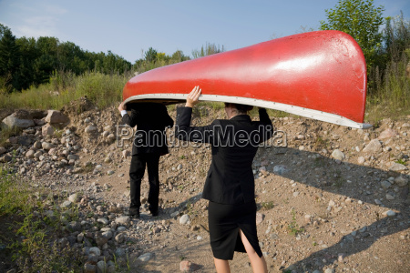 business people carrying canoe