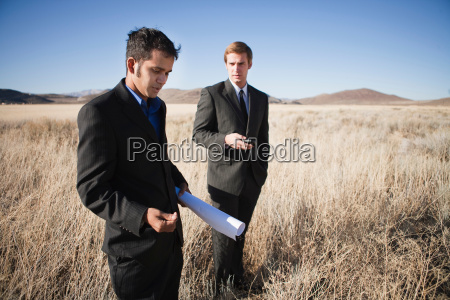 two men with blueprints in field