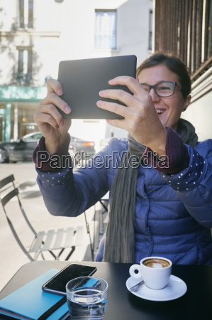 mid adult woman taking digital tablet
