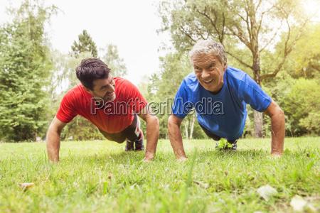 two men doing push ups outdoors