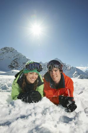 couple lying in snow kuhtai austria