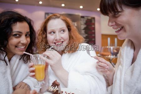 women drinking juice in cafe
