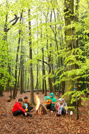 friends sitting around campfire together