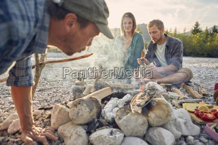 adults sitting around campfire preparing food