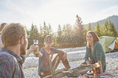 adults sitting around campfire making a