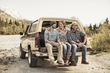three people sitting on back of
