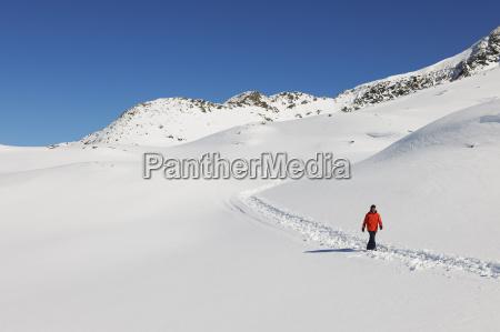 man wlaking in snow kuhtai austria