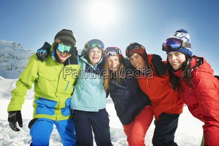 friends wearing skiwear with arms around