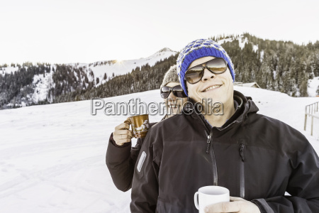 friends enjoying coffee on snow covered