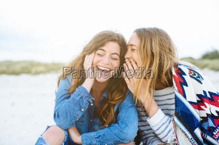 duas jovens amigas sussurando na praia