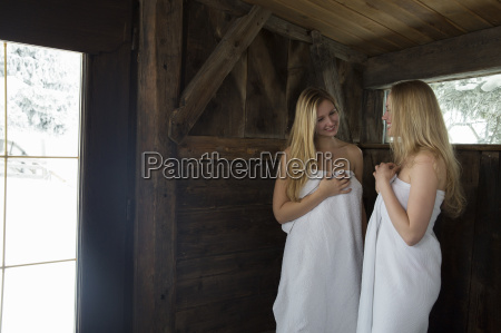 two young women standing in sauna