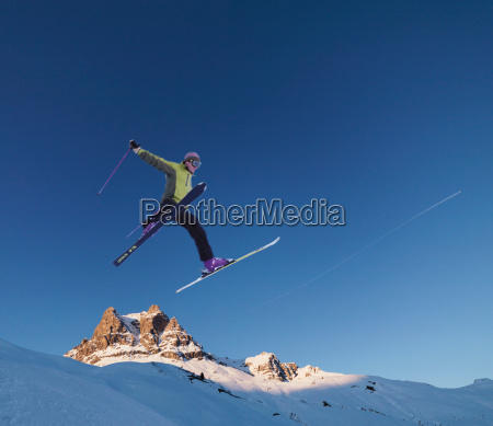 skier jumping across skyline