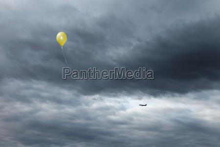 yellow balloon floating toward cloudy sky