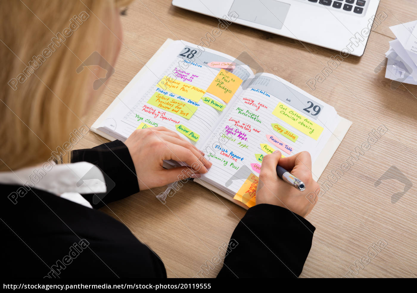 businesswoman, writing, schedule, in, diary - 20119555