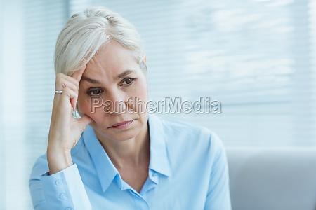 mulher senior triste em casa