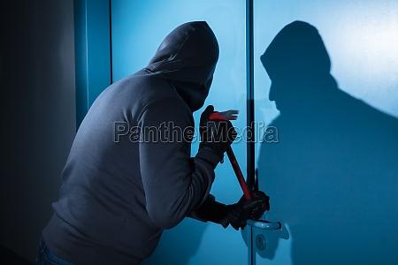 ladrao tentando quebrar a porta
