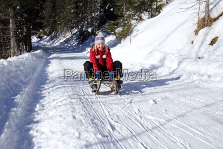girl sledding in the winter