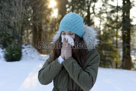 teenage girl wearing woolly hat blowing