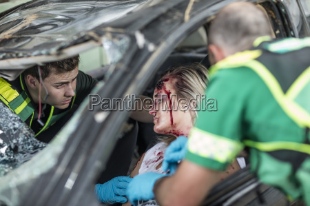 paramedics helping car crash victim after