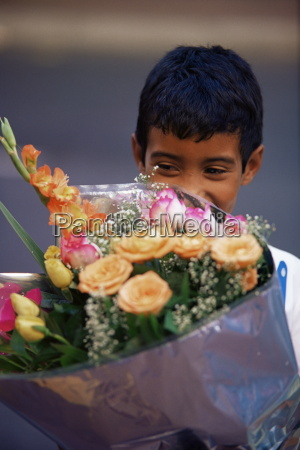 young boy holding flowers at the