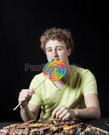 homem novo com lollipop e doces