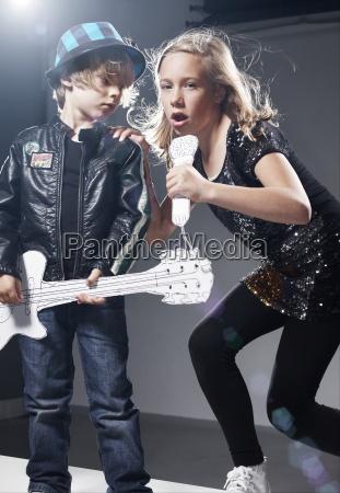 girl and boy playing band on