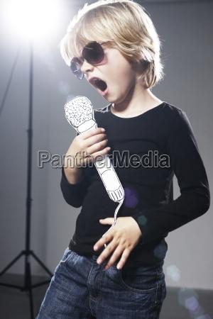 boy singing in paper mircophone against