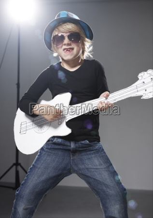 boy playing paper guitar against grey