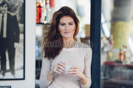smilende kvinde udendors bedrift kop kaffe
