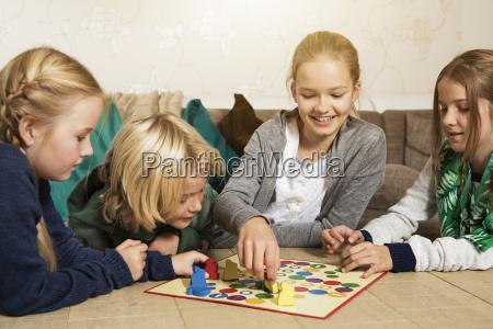 quatro criancas que jogam o ludo