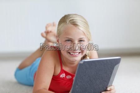 smiling blond girl using digital tablet