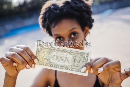 frau zeigt eine dollar banknote nahaufnahme