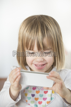 smiling little girl with smartphone