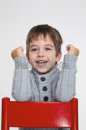 portrait of boy sitting on red