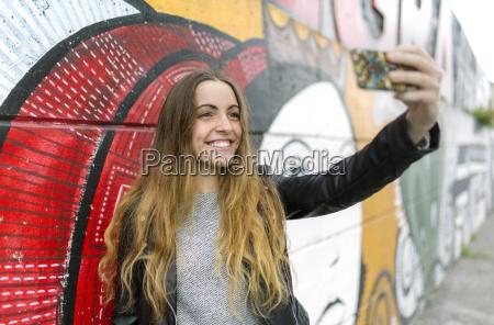 sorrindo, menina, adolescente, levando, um, selfie, em, mural - 21107309
