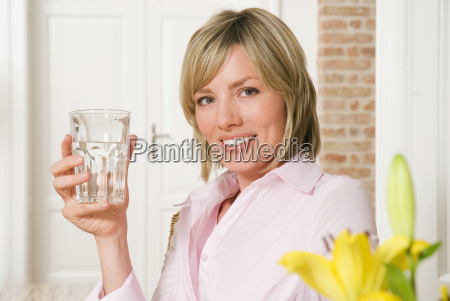 young woman holding a glass of