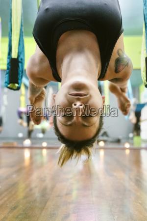ioga aerea praticando da mulher na