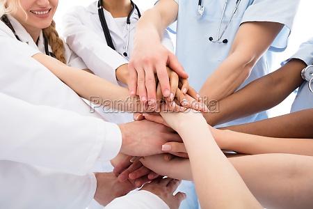 grupo de doutores que empilham suas