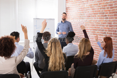 group of businesspeople raising hands in