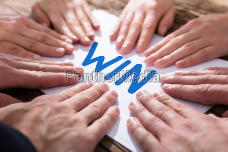 hands on paper showing win concept