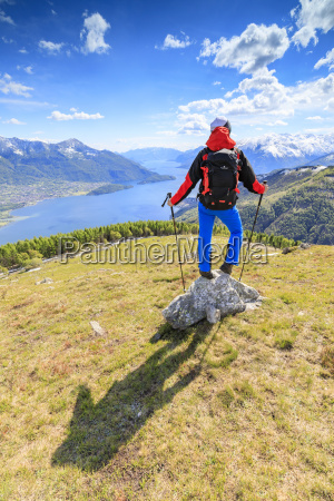 hiker on green meadows admires lake