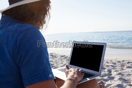 man using laptop on the beach